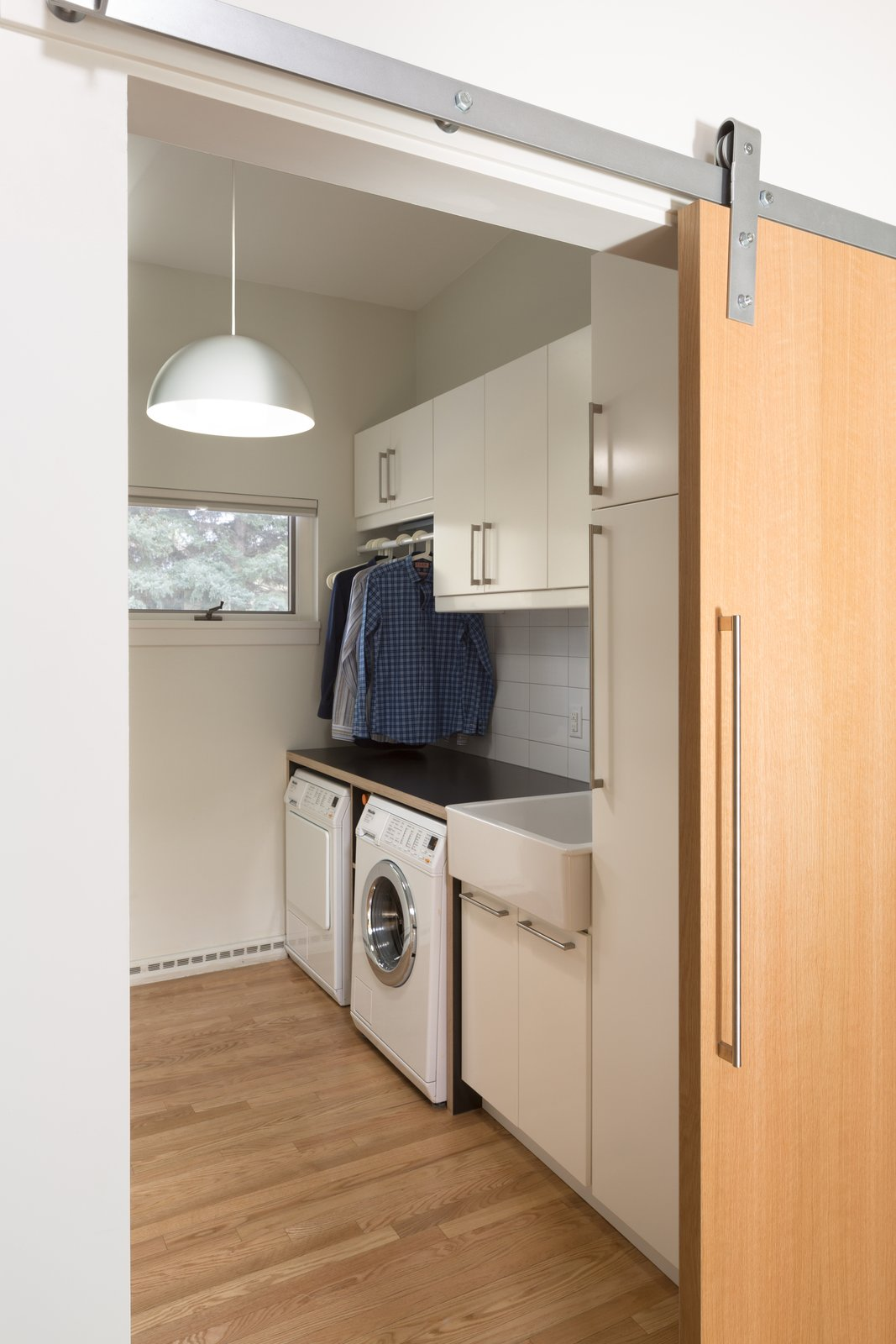 Laundry Room, Side-by-Side, Laminate Counter, and White Cabinet Laundry Room. Ikea build out with a custom made Melamine waterfall countertop over washer and dryer. Interior barn door is white oak slab with low luster natural finish.   Langley_Hawthorne Residence by Design Platform