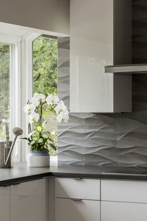 Detail of natural stone backsplash by Decorative Materials Inc. High gloss white cabinets by Vogo.