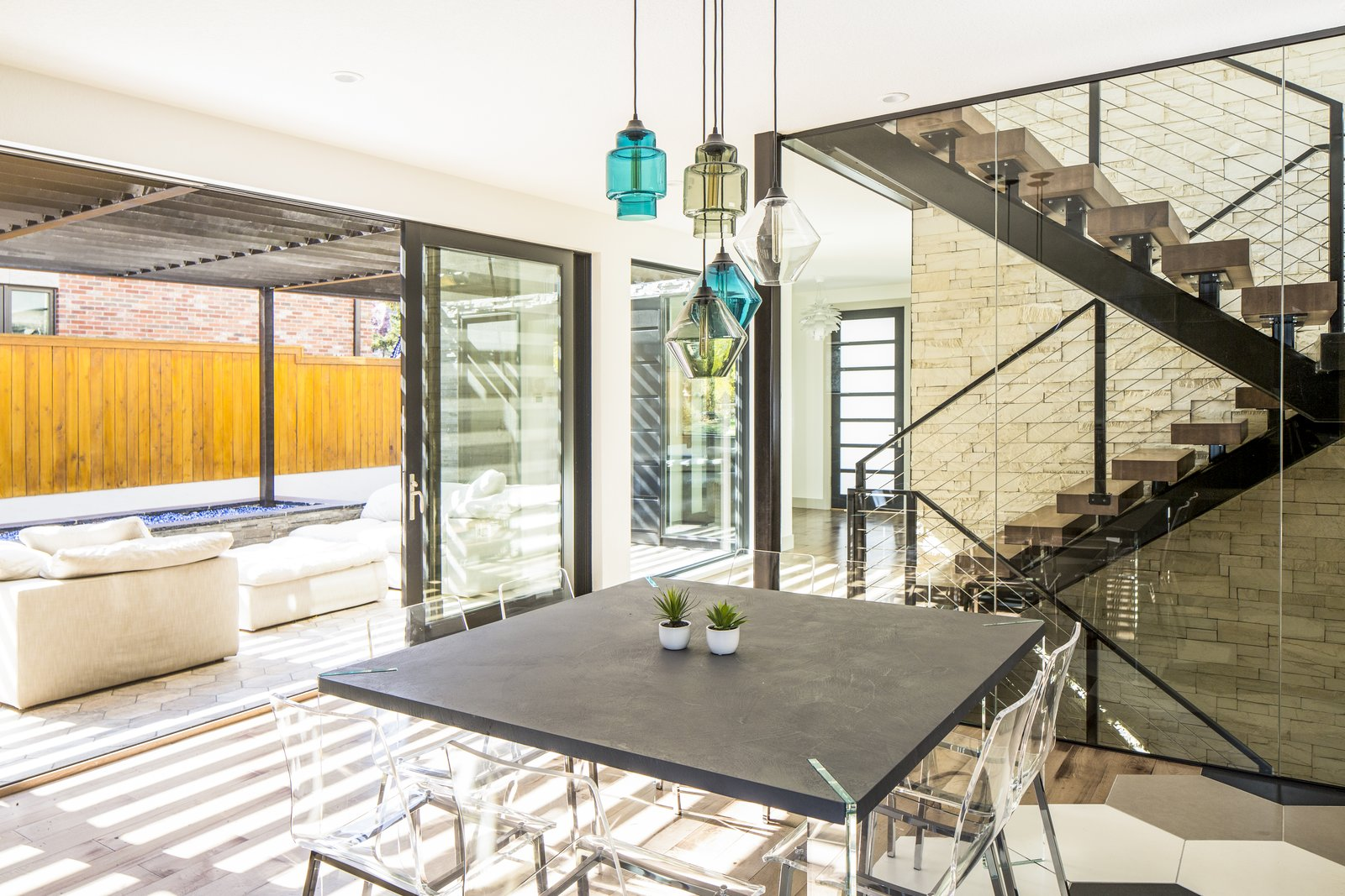 Dining Room, Chair, Table, Gas Burning Fireplace, Medium Hardwood Floor, and Pendant Lighting Dining area opens to exterior lounge and firepit. Steel and maple butcherblock staircase with stone wall and floor to ceiling glass enclosure.   Hilltop Residence by Design Platform