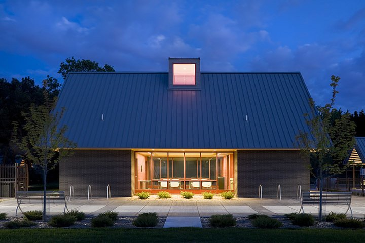 Elevation of the brick park building at dusk.  A modern and fresh approach to a small public park in Minnesota.