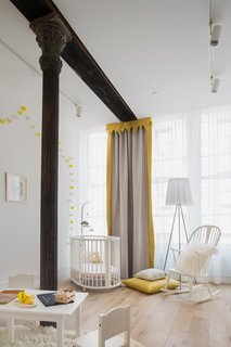 In an otherwise tame Tribeca apartment designed by London-based Melanie Williams Bespoke Interiors, a splash of color in the nursery adds a fun and playful feel to the space. Gray and yellow curtains are set up to create a little theater space in the bedroom.