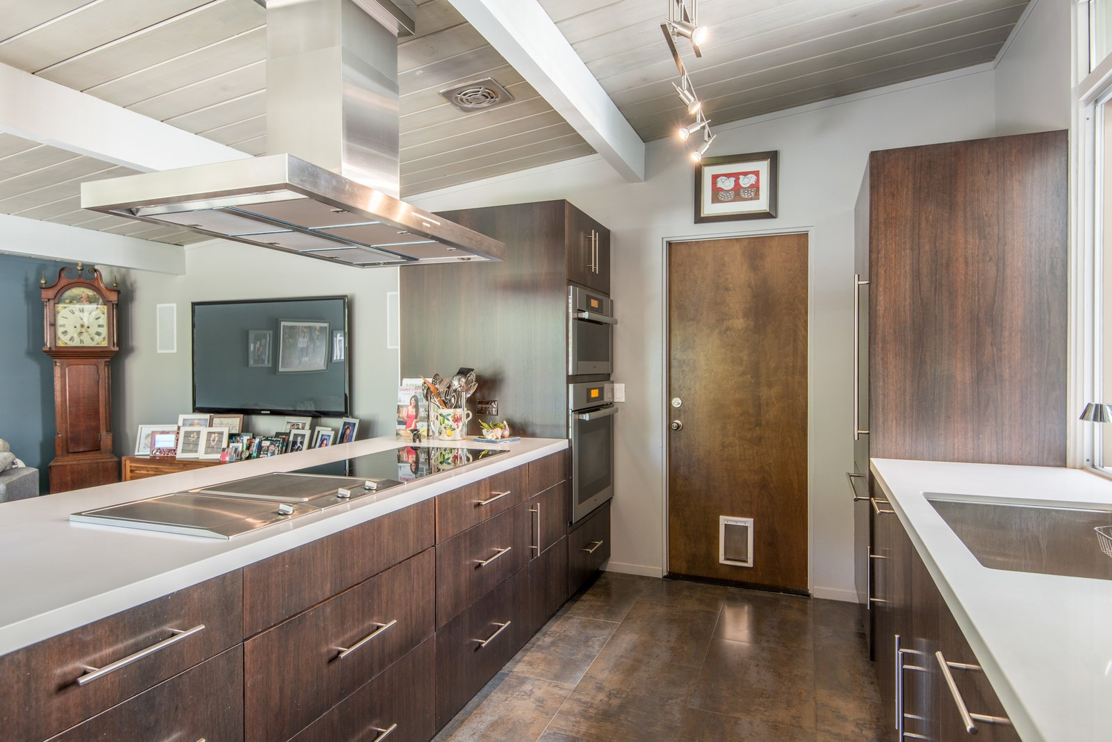 Kitchen, Range Hood, Wood Cabinet, Wall Oven, Porcelain Tile Floor, Dishwasher, Refrigerator, Track Lighting, Engineered Quartz Counter, Cooktops, and Undermount Sink Crystal Cabinetry and Miele appliances  Sunnyvale Eichler Remodel