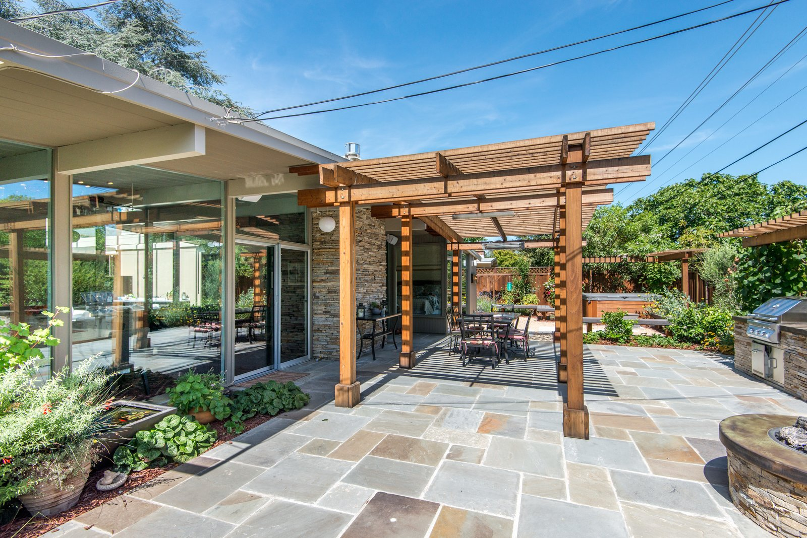 Outdoor, Wood Patio, Porch, Deck, Back Yard, Stone Patio, Porch, Deck, Landscape Lighting, Flowers, Hardscapes, and Hot Tub Pools, Tubs, Shower An outdoor dream - serene and functional for entertaining guests, or just relaxing  Sunnyvale Eichler Remodel