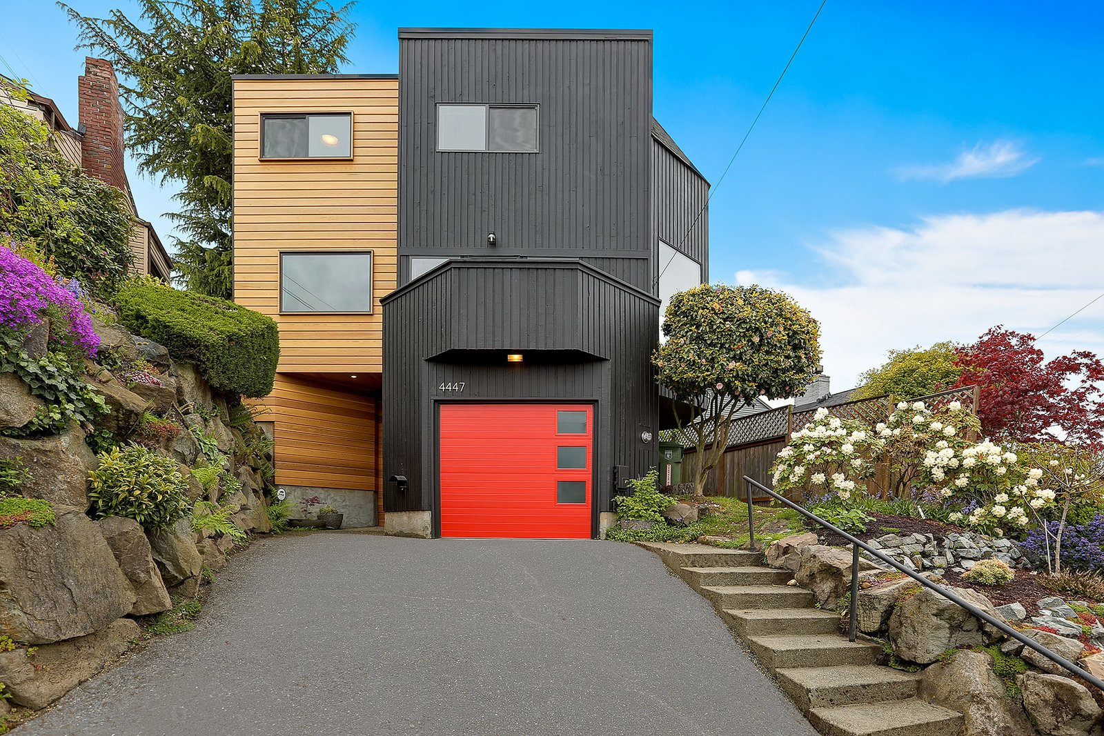 The front of the Monolith is framed by granite and basalt rock walls and features clear cedar siding, Sherwin Williams Tricorn Black painted wood siding, and Sherwin Williams Tomato red custom painted Clopay garage door.  The Monolith