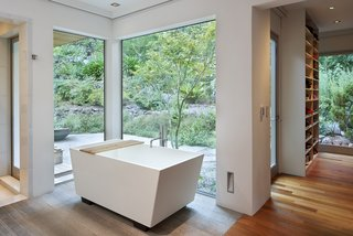 """Tōrō House is a study in the harmony of dualities,"" says architect Mark English. Inspired by Japanese design, the home harmoniously unites with nature—as seen here in the master bathroom, where the tub overlooks the outdoor space."