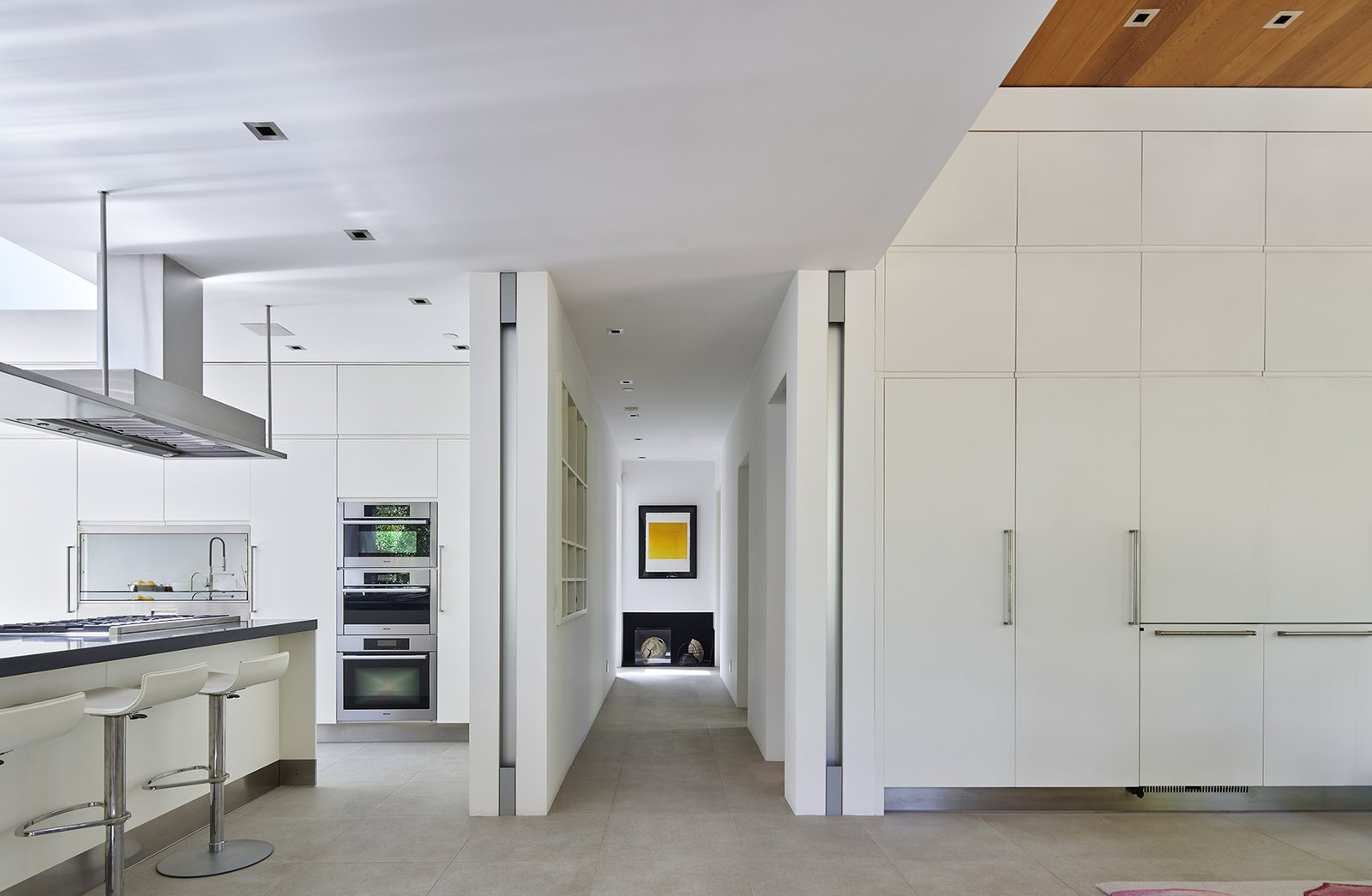 Kitchen, Microwave, Cooktops, Ceiling Lighting, Porcelain Tile Floor, Range Hood, Dishwasher, Undermount Sink, Wall Oven, Refrigerator, White Cabinet, Engineered Quartz Counter, and Mirror Backsplashe Entry, kitchen, dining.  The TORO House by Mark English