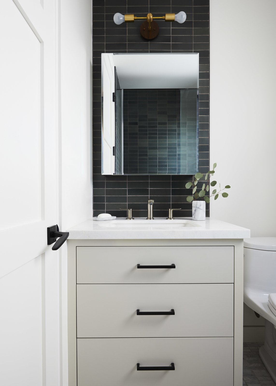 Bath Room, Wall Lighting, Ceramic Tile Wall, Marble Counter, and Undermount Sink Guest Bathroom  The Strand Residence