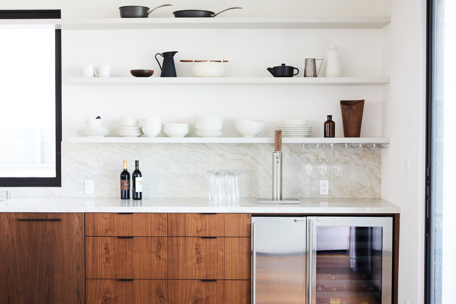 Kitchen, Marble Counter, Beverage Center, Wine Cooler, Stone Slab Backsplashe, and Open Cabinet Kitchen  The Strand Residence