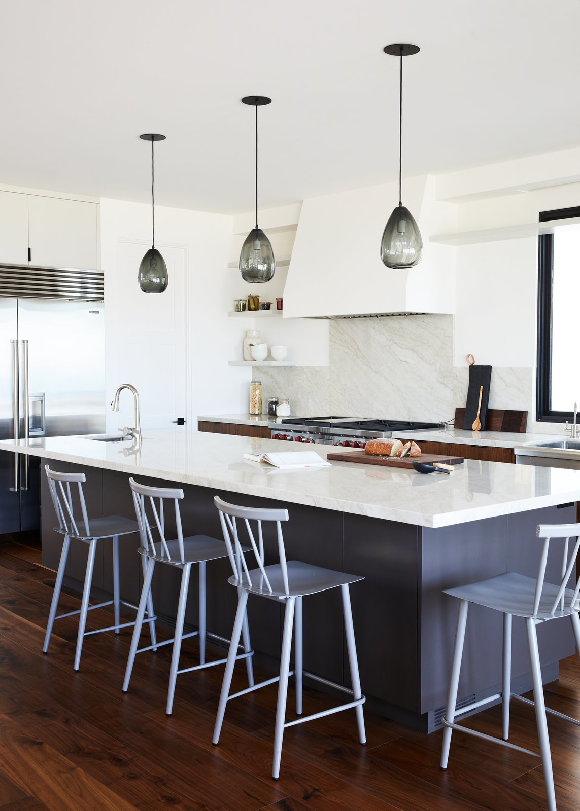 Kitchen, Dark Hardwood Floor, Pendant Lighting, Refrigerator, Medium Hardwood Floor, Marble Counter, Range Hood, Range, Open Cabinet, and Stone Slab Backsplashe Kitchen  The Strand Residence
