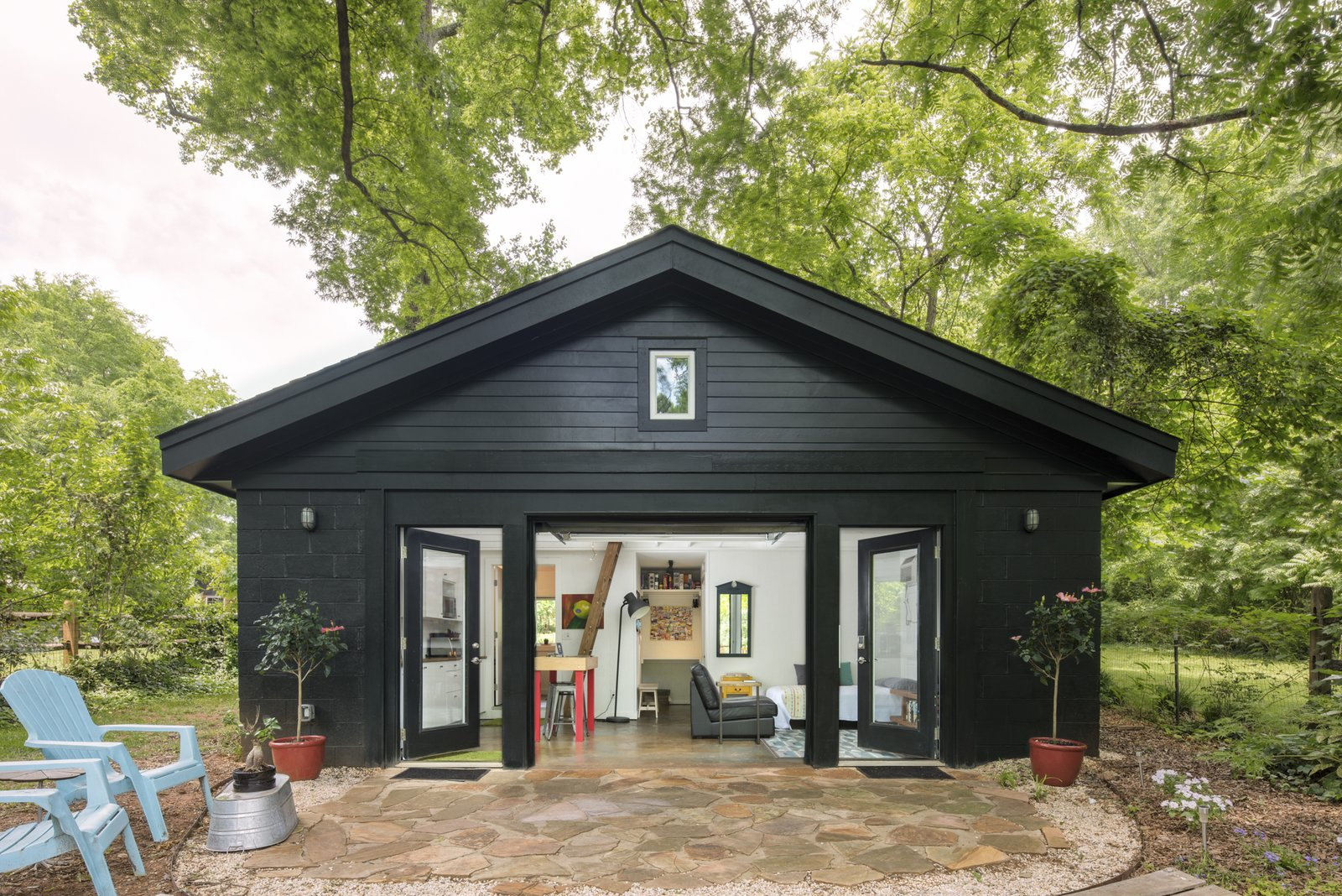 Concrete Siding Material, House Building Type, Living Room, Trees, and Back Yard The old garage is now an eclectic, modern, tiny home.   SvartKub