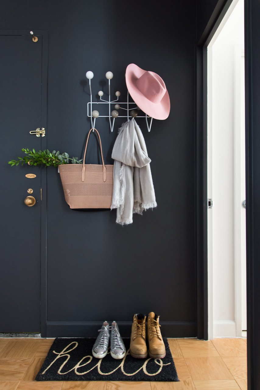 While black walls aren't the first thing you may consider for an inviting foyer, the dark walls are often in soothing contrast to the bright sunlight directly outside. The dramatic bold color also brings anything bright and colorful into stark relief.  Photo 4 of 12 in The Power of Color and What Each Shade Is Best For