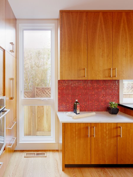 In this California home, a red mosaic tiled backsplash balances the lower white marble counter and wood cabinets. A mosaic tiled backsplash is generally budget-friendly and even a possible DIY project because they're typically already mounted to a backing and come in sheets.