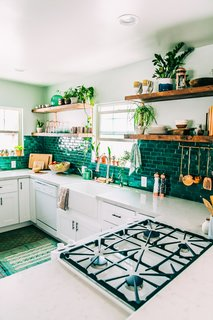 These green tiles are a perfect backdrop for the wealth of potted plants lining the shelves and window sills in this LA artist's kitchen.