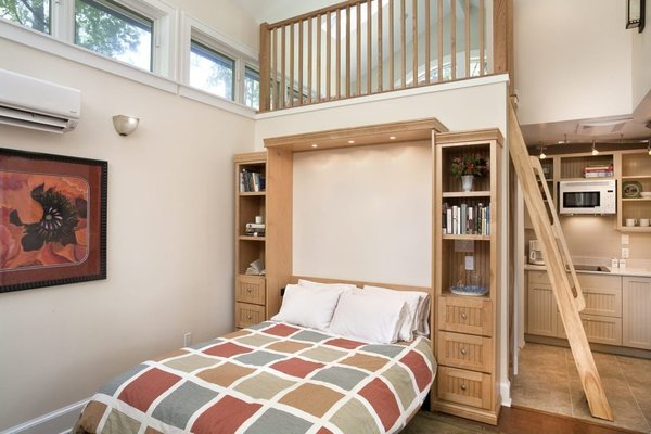 Built-ins, such as this Murphy Bed wall, accommodate living in a small footprint. The ladder accesses a small loft above the bathroom.