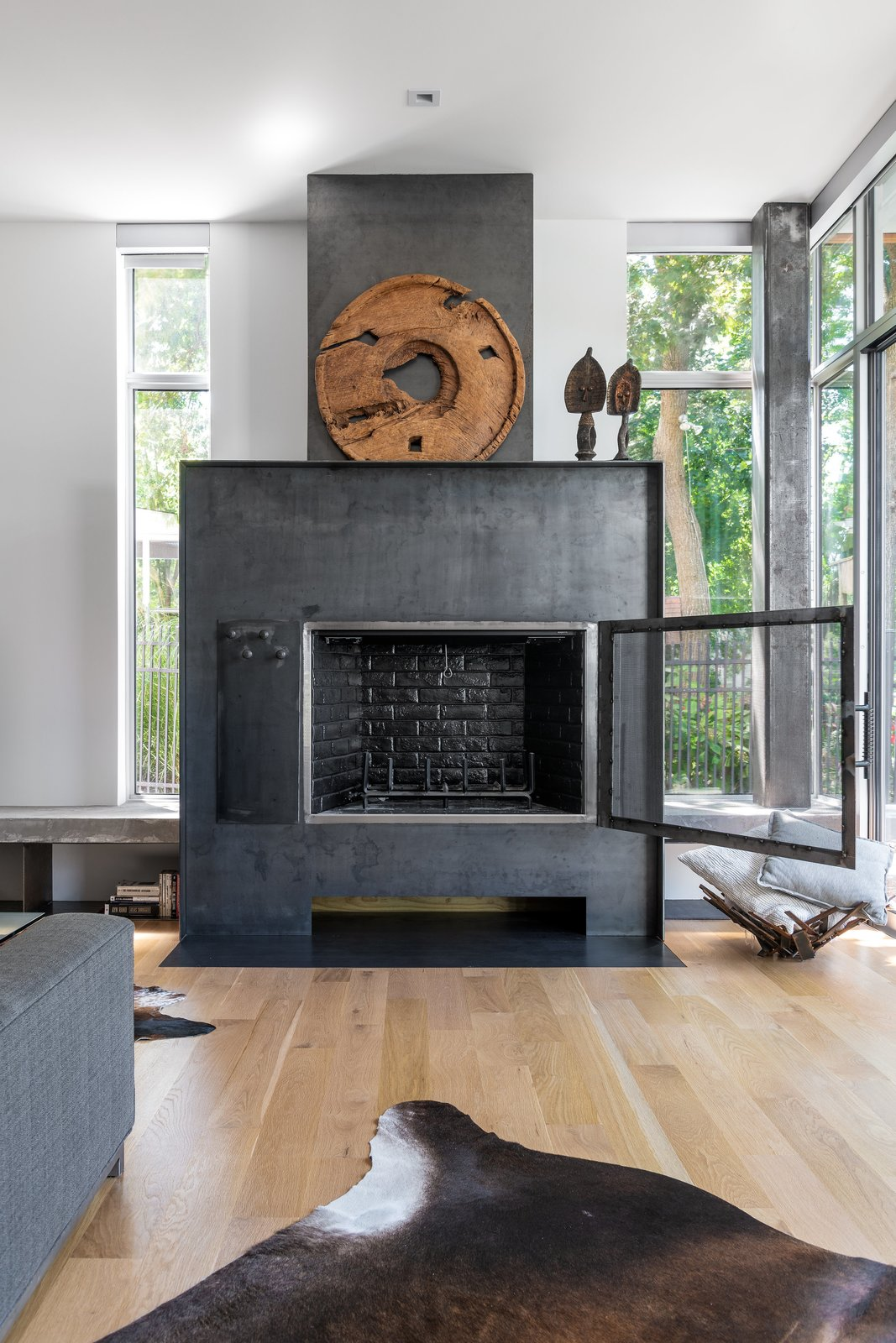 Living Room, Standard Layout Fireplace, Wood Burning Fireplace, Sofa, Light Hardwood Floor, Ceiling Lighting, Recessed Lighting, Bookcase, and Bench Fireplace Detail w/ Custom Hinged Screen  Spa Creek House by GriD