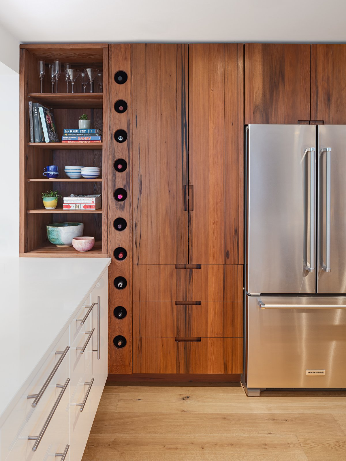 Kitchen, Refrigerator, Engineered Quartz Counter, Wood Counter, White Cabinet, Wood Cabinet, and Light Hardwood Floor Custom spring loaded wine rack made with reclaimed American redwood   Wayne Residence