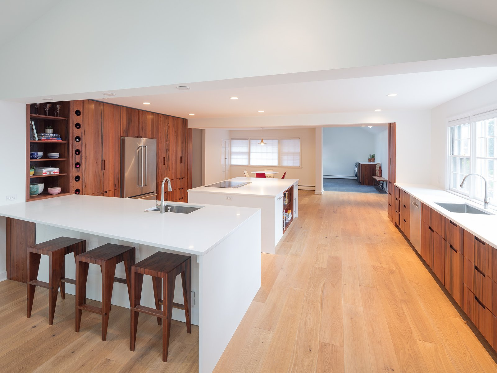 Kitchen, Refrigerator, Engineered Quartz Counter, White Cabinet, Cooktops, Wood Cabinet, Light Hardwood Floor, Recessed Lighting, and Undermount Sink contrasting high gloss quartz counters with reclaimed American redwood cabinet fronts  Wayne Residence