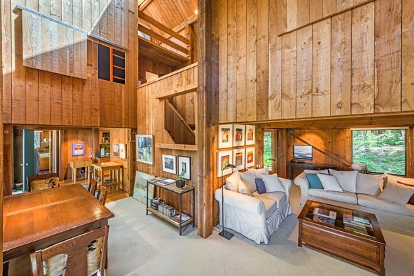 A look at the living and dining room, with barn-style doors and openings. Shown here, the original 1968 redwood interior was completed by master craftsman Matthew Silvia.