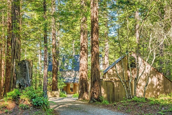 A drive through the redwood forest leads to the home's entrance. The home sits on 1.6 acres with permanently protected forest and ocean views.