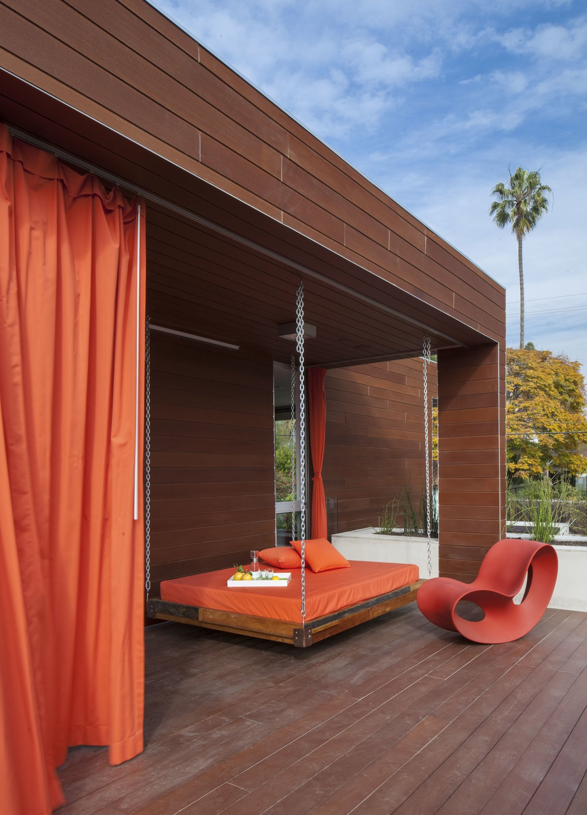 Outdoor, Large Patio, Porch, Deck, Back Yard, Hanging Lighting, Wood Fences, Wall, Wood Patio, Porch, Deck, Trees, and Horizontal Fences, Wall An outdoor swing bed makes the most of sunny, Santa Monica weather.  Dawnsknoll by Minarc