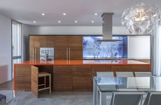 "Colors from dramatic, Icelandic landscapes inspired the contrasting interiors. Volcanic orange creates a multifunctional gathering point at the heart of the home while the swimming pool brings in a lagoon hue; the cabinets recall glaciers and lava. In the kitchen, ""disappearing"" chairs are stored under the island to maximize space."
