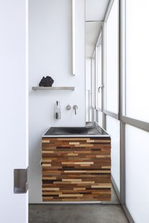 This prefabricated home in California sought to minimize waste in everything from the construction process to the appliances and fixtures inside. The sink in the powder room is made from recycled tires.