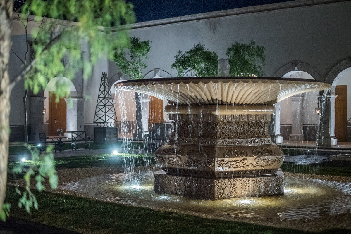 The outdoor water feature does double duty; it also serves as a water replenishment well for plants and vegetation.  Photo 15 of 15 in Patrón Designed a Spanish Colonial Guest House with Modern Flair