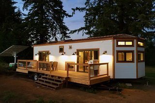 This tiny house on wheels is by Tiny Heirloom. To make the home more eco-friendly, the owner installed a solar panel nearby to generate power.