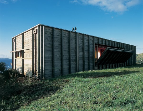 Located on New Zealand's North Island along the Coromandel Peninsula, this timber-clad shipping container house by Crosson Clarke Carnachan Architects captures the simplicity of living with nature. An open-plan layout extends the interior toward the surrounding landscape and ocean, while a built-in mechanism reveals a drop-down deck on one side of the unique holiday home.