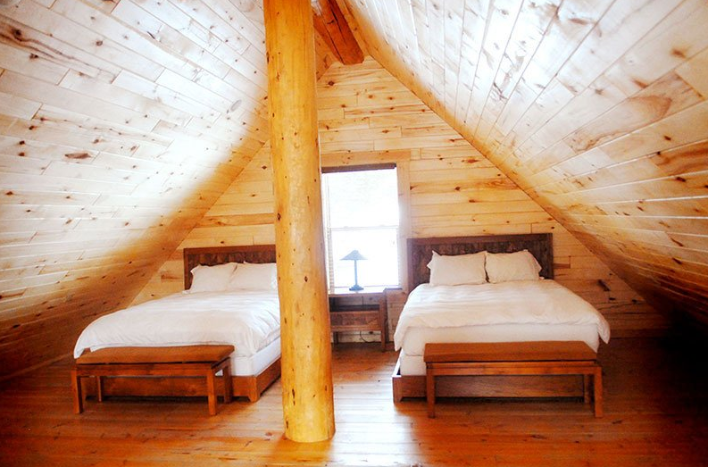Bedroom, Bed, and Medium Hardwood Floor Enjoy a touch of luxury in these modern cozy log cabins. Rustic at heart, each cabin houses either a 1 or 2 bedroom layout, a loft with 2 queen beds, fireplaces, stovetops (no ovens) and spa-inspired bathrooms. Step outdoors and enjoy the surrounding Chalk Cliff views from your private deck or patio. All Cabins are a short walk to any of the natural hot spring pool areas and the Spa and Club at Mt. Princeton.  Photo 7 of 12 in 11 A-Frame Cabins For A-Grade Getaways