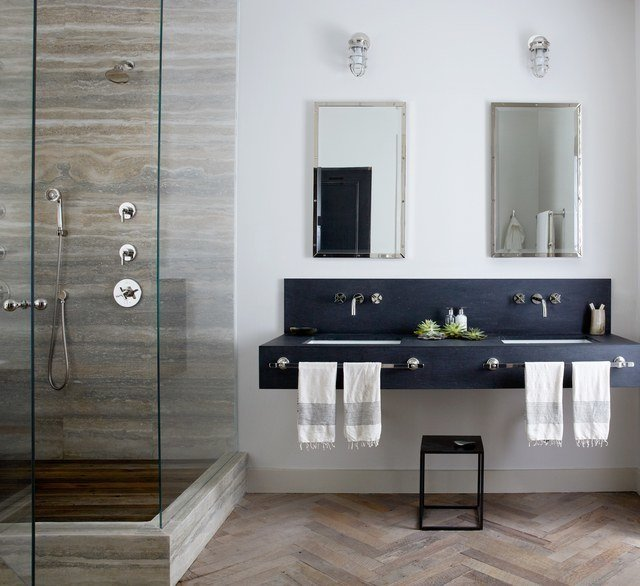 New York City–based designer Jenny Wolf  used mirrors and patterns for this windowless bathroom. Tall mirrored medicine cabinets and a glass shower amplify light from the interior fixtures, brightening up the space. Wolf used built-in cabinets to save floor space. A herringbone wood floor gives the illusion of a larger and warmer bath.  Photo 11 of 11 in These 10 Designers Are Experts at Creating Colorful Bathrooms That Pop