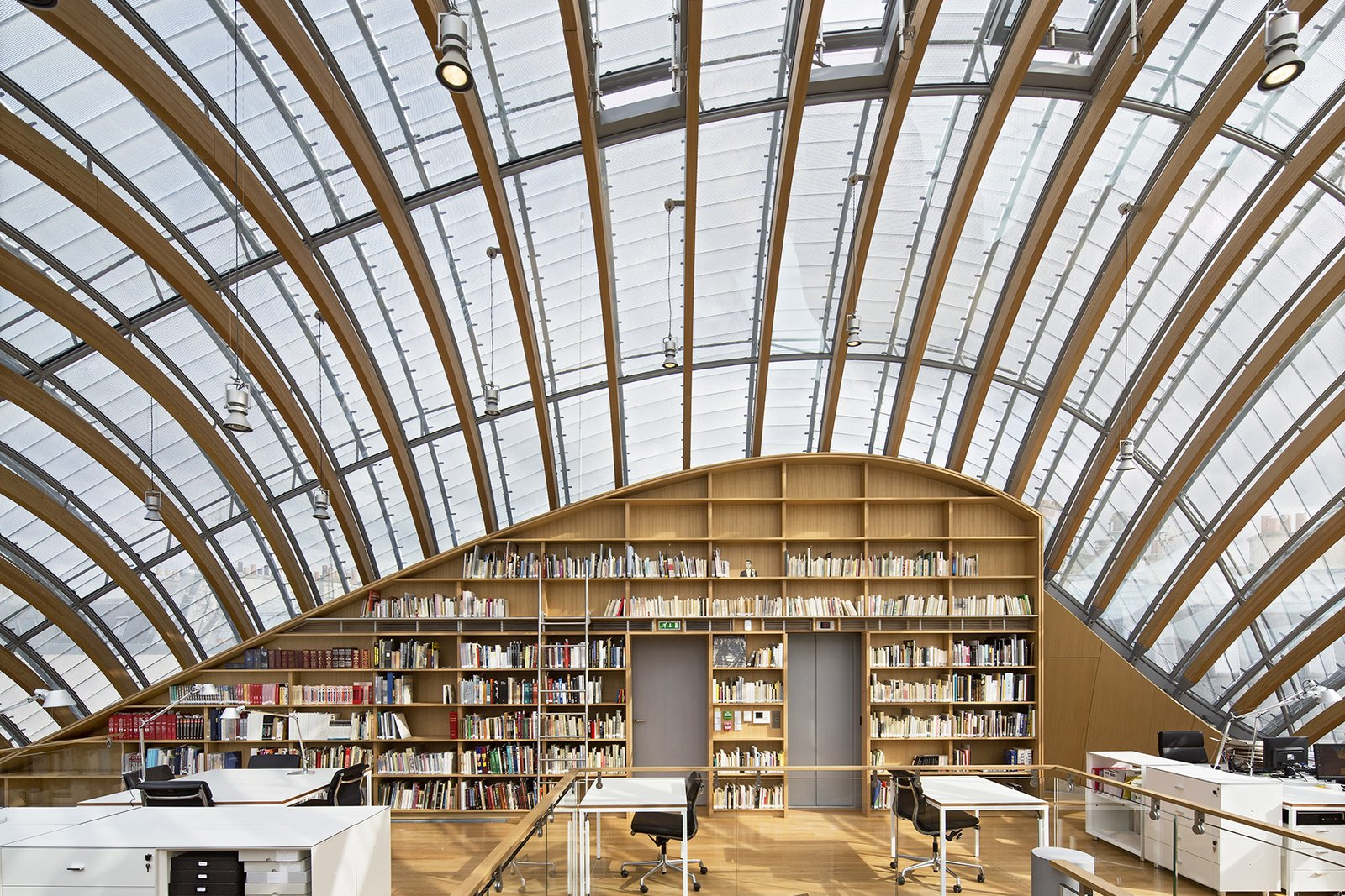 Office, Bookcase, Light Hardwood Floor, Chair, Library Room Type, Desk, Shelves, Lamps, and Storage Imitating the form of an armadillo, this critically acclaimed (some critics have called this one of Renzo Piano Building Workshop's best works) 23,000-square-foot, five-story structure houses offices, archives, exhibition space, and a 70-seat screening room for the foundation is dedicated to celebrating the legacy of the pioneering French film company.  Photo 6 of 13 in 12 Renzo Piano Buildings We Love