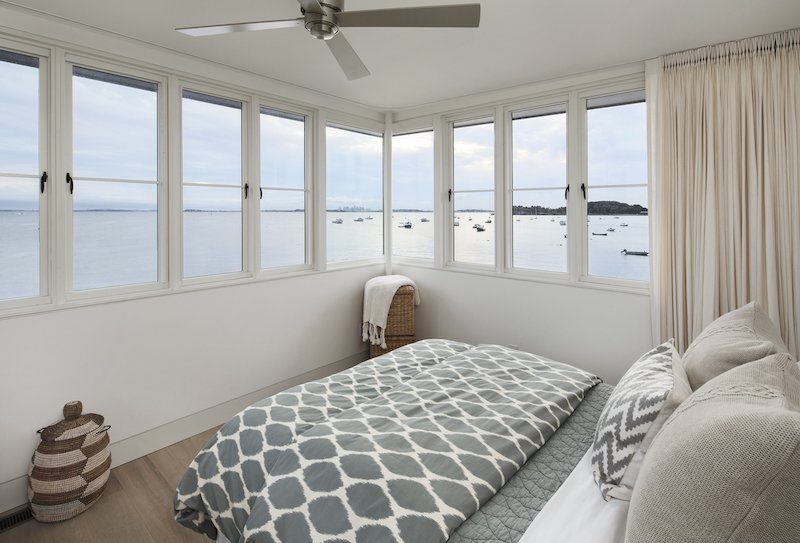 Bedroom, Bed, and Light Hardwood Floor The view from the tower bedroom, Boston in the distance.  The Lighthouse