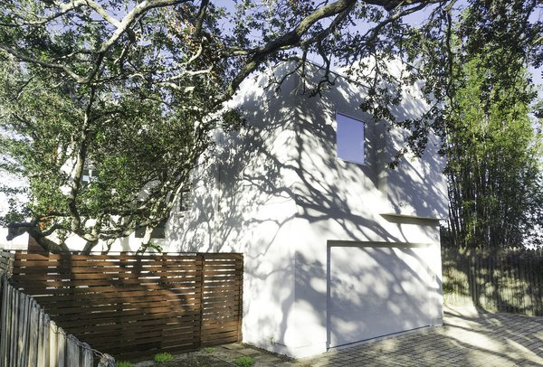 South Side/Garage-The home is designed as a U-Shape creating a courtyard around the large Live Oak Tree.  The site is designed to absorb 100% of the water that falls on the site.
