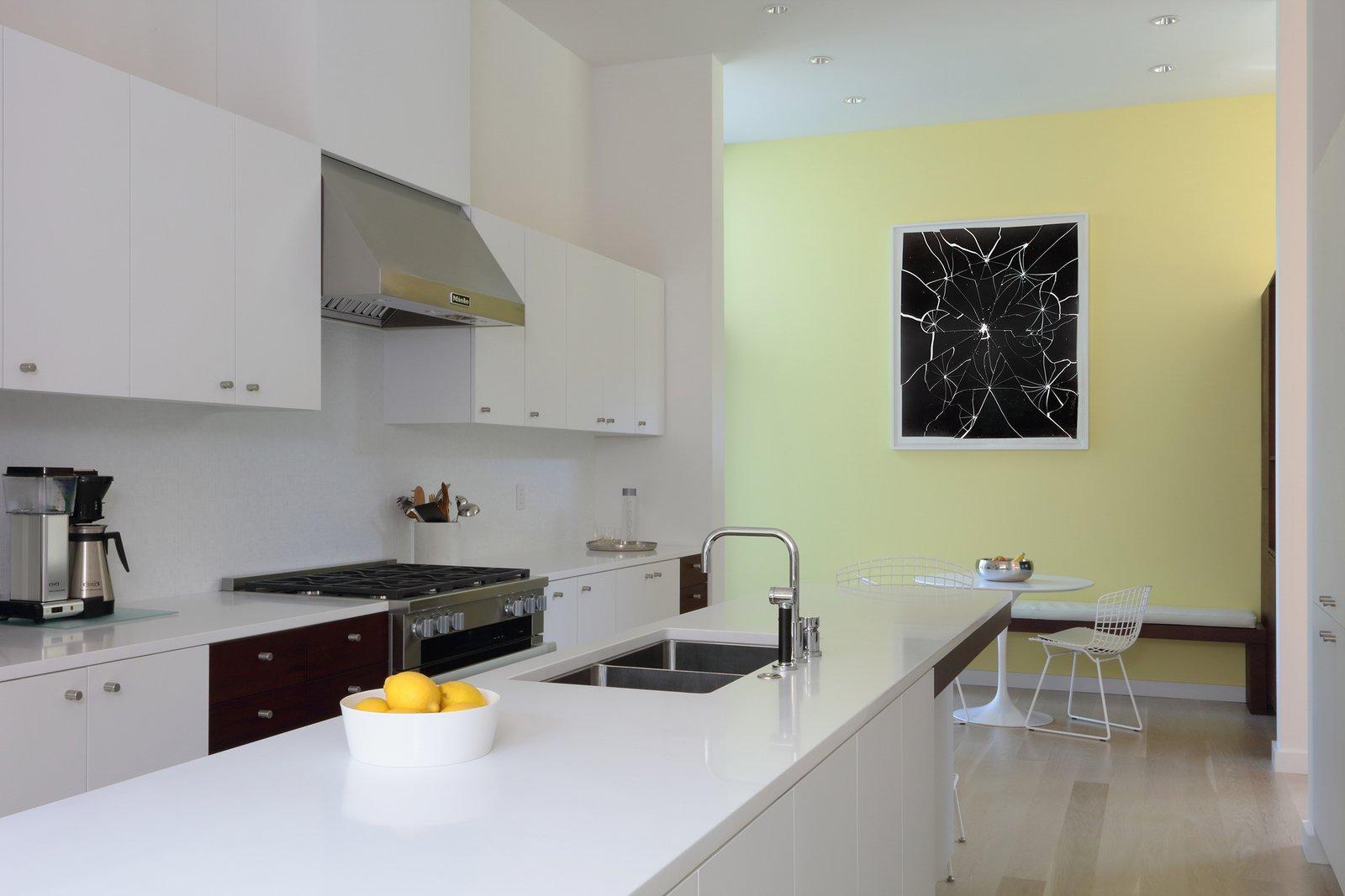 Kitchen, Engineered Quartz Counter, Light Hardwood Floor, White Cabinet, Wood Cabinet, Glass Tile Backsplashe, Ceiling Lighting, Range, Range Hood, and Undermount Sink Kitchen  The Hearn House