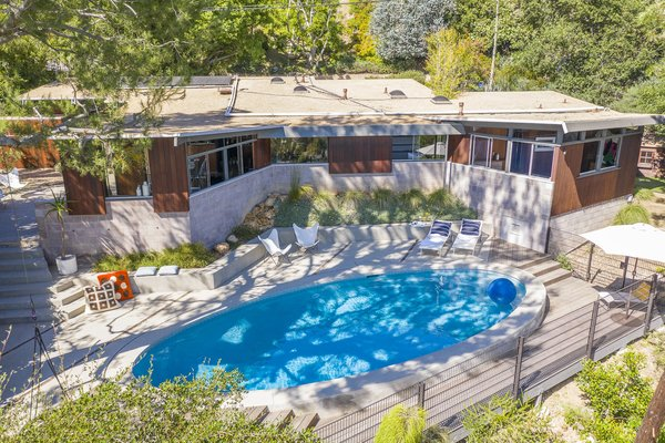 The spacious backyard features a pristine hillside pool and hardscape overlooking panoramic views from the Santa Monica Bay all the way to Catalina.