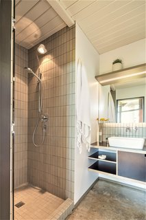 Vertical tiles line the shower and the faucet backsplash.