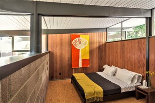 A look at another bedroom, fitted with wood paneling, exposed cement, and cork flooring.
