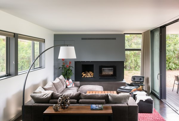 Modern open concept living room in Boulder with a fireplace, gray and white walls, wood floors. Large slider opens to backyard.  Sunset House by HMHAI