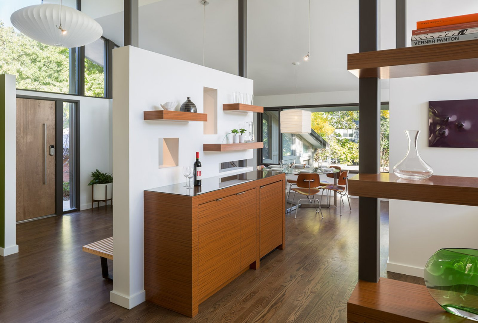 Removing a massive fireplace from the center of the home and replacing it with much smaller art-wall and built-ins creates a visual connection, making the spaces feel larger without adding on.  Mid Century Re-Modern by HMHAI