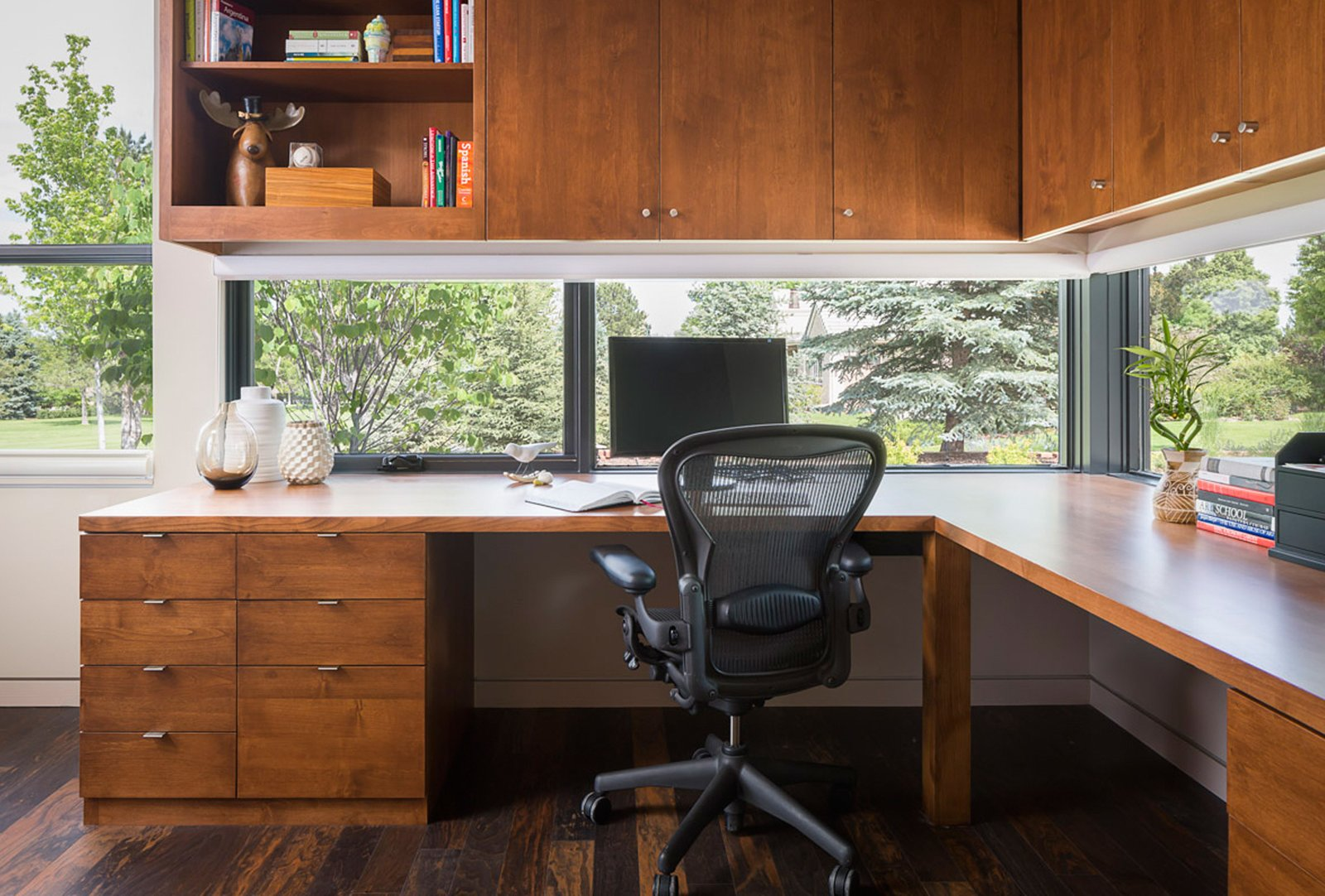 Windows at the desk level are integrated into the cabinets and provide views of the golf course.  Modern Golf Course Home by HMHAI