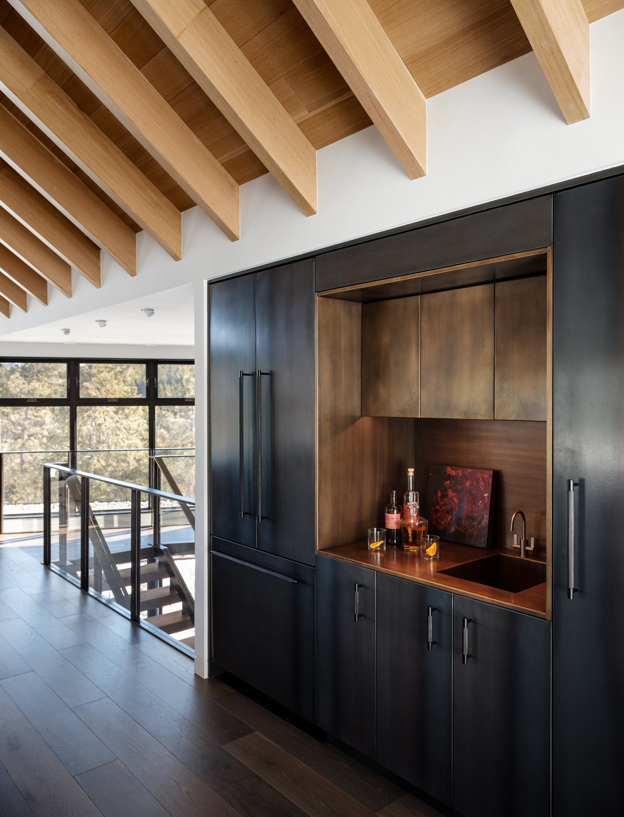 Kitchen, Metal Counter, Beverage Center, Metal Cabinet, Refrigerator, Undermount Sink, and Dark Hardwood Floor We think this centrally located custom metal/brass bar is an entertainers dream!   Modern Cabin by HMHAI