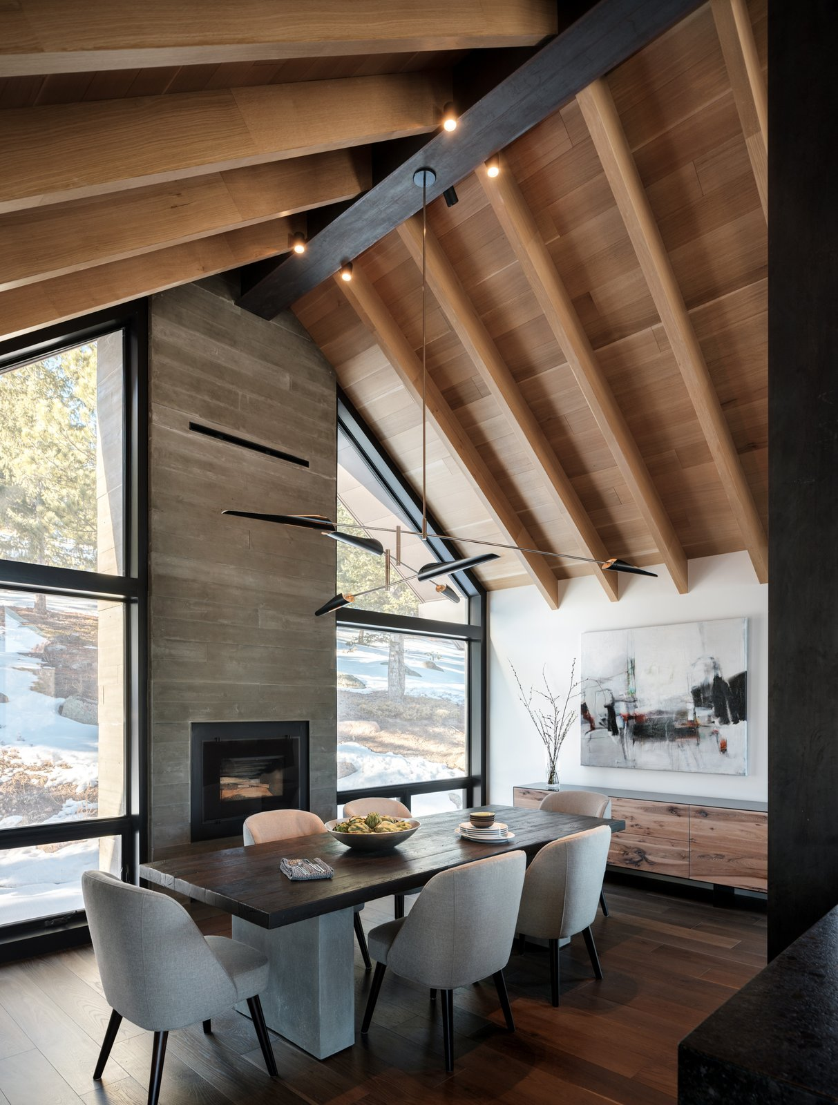 Dining Room, Table, Accent Lighting, Chair, Storage, Pendant Lighting, Dark Hardwood Floor, and Gas Burning Fireplace Dining rooms don't have to be overly formal and stuffy. We especially love the custom credenza and the Sarus Mobile  Modern Cabin by HMHAI