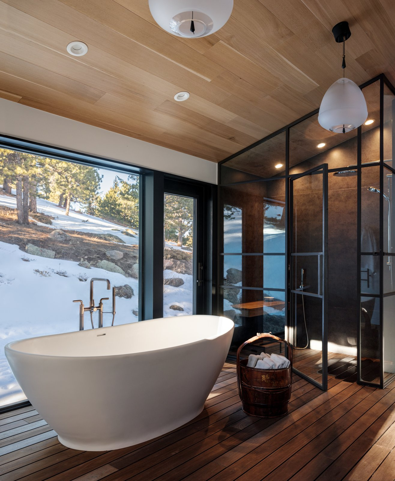 Bath, Freestanding, Medium Hardwood, Enclosed, and Pendant The large floating bathtub invites relaxation and serenity.  Bath Enclosed Medium Hardwood Photos from Modern Cabin