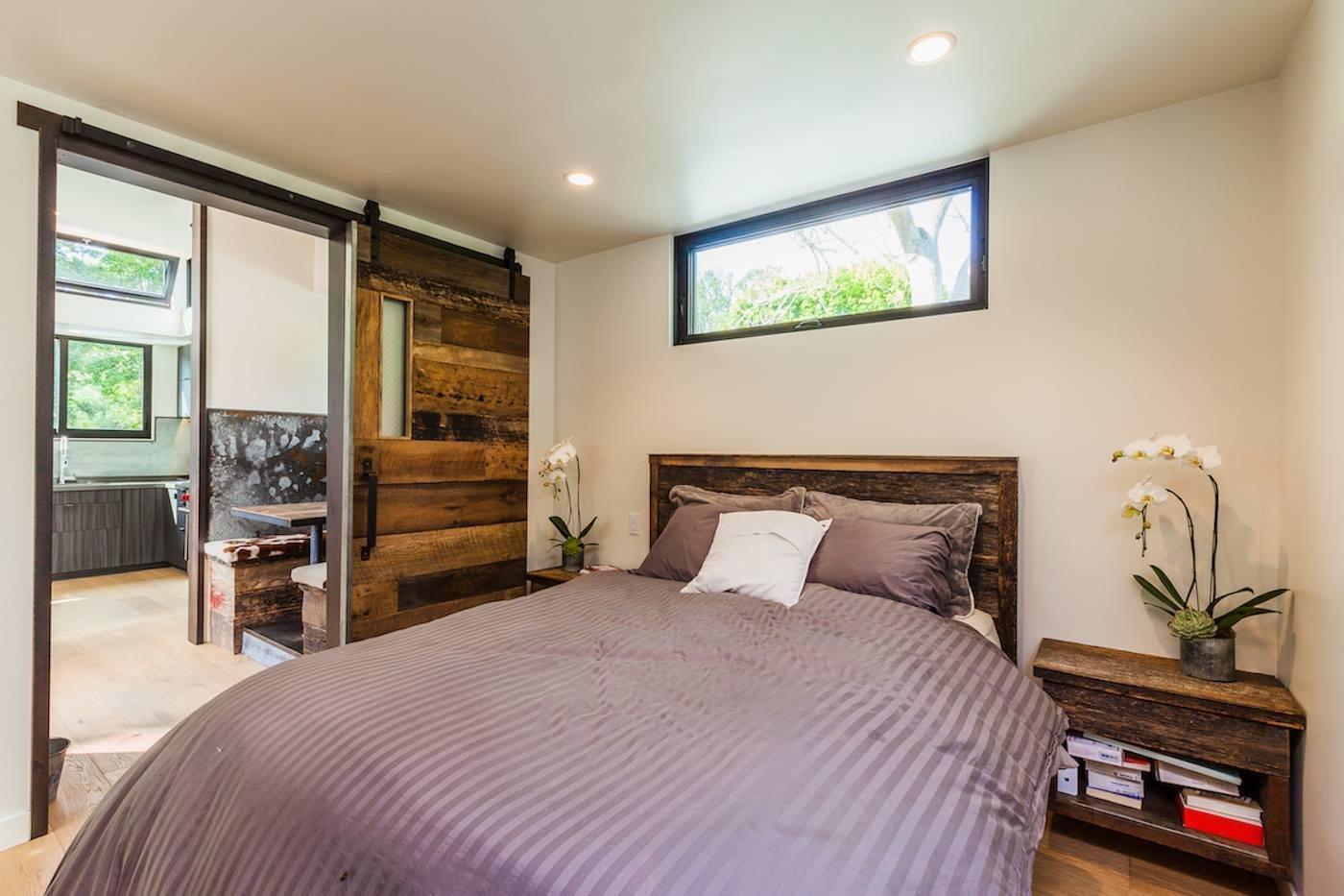 Bedroom, Bed, Night Stands, Light Hardwood Floor, and Ceiling Lighting Reclaimed Steel and Wood Barn Doors  Reclaimed Malibu Modern Beach Retreat