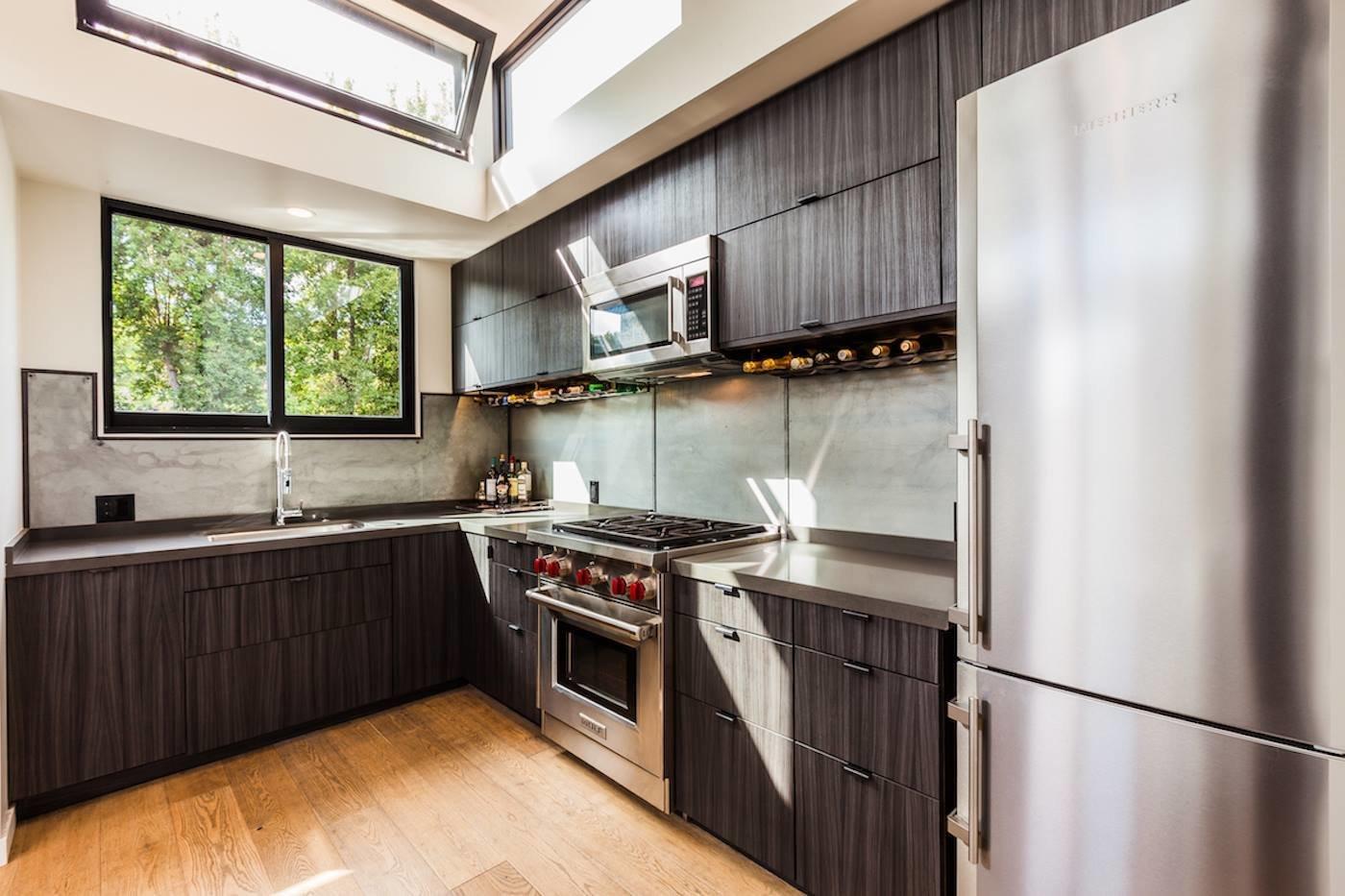 Kitchen, Metal Backsplashe, Refrigerator, Quartzite Counter, Light Hardwood Floor, Range, Dishwasher, Microwave, Undermount Sink, and Ceiling Lighting Clean Custom Kitchen  Reclaimed Malibu Modern Beach Retreat