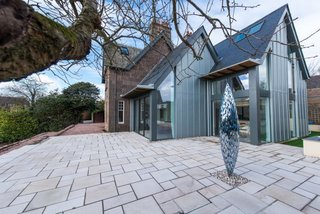In 2016, Hyve Architects completed the renovation of The Gables, a heritage home in Stonehaven. A modern extension features an open kitchen and family room that connects to the main stone home. The double-pitched roofline of the new structure references the end gable line of the original house.