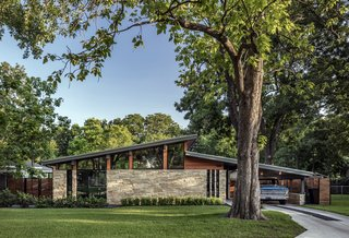 "When Austin-based firm Matt Fajkus Architecture was tasked with renovating this classic midcentury home, they sought to open up the interior—not only by unifying the common areas into an open-plan layout, but also by literally raising the home's roof. This strategy increased the ceiling height on three sides of the home, allowing for the insertion of clerestory windows to create a bright and airy open living space. ""The raised ceiling maintains the original pitched roof geometry to stay harmonious with the existing gabled roof in the private zone,"" explain the architects in a statement."