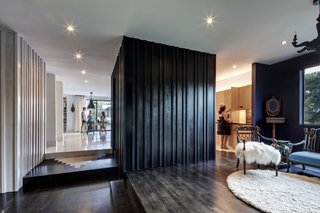 Black walls were used to create contrast, and the black board-and-batten box is the powder room that separates the kitchen and the hallway with a glimpse of the living area beyond. The kitchen, living, and dining areas extend out to the exterior deck.