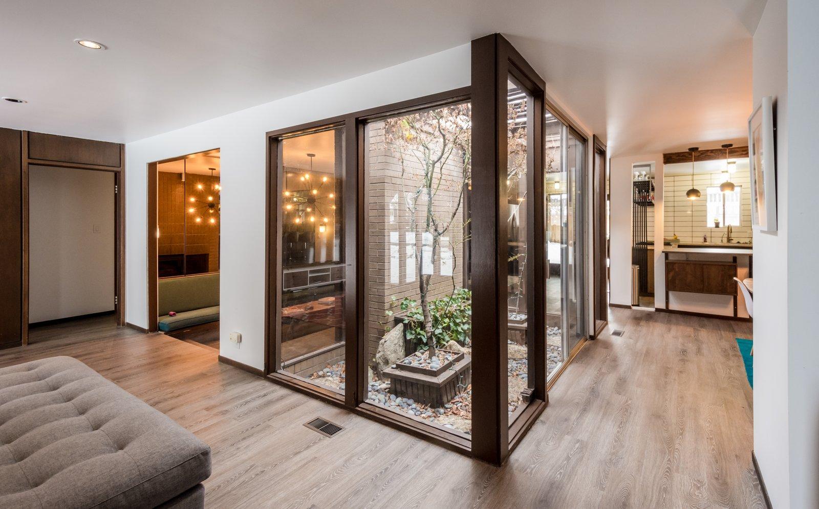 Entry of home showcasing the original atrium new flooring and open floor plan  Ron Molen Revival